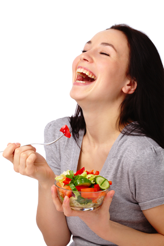 Woman laughing alone with salad1